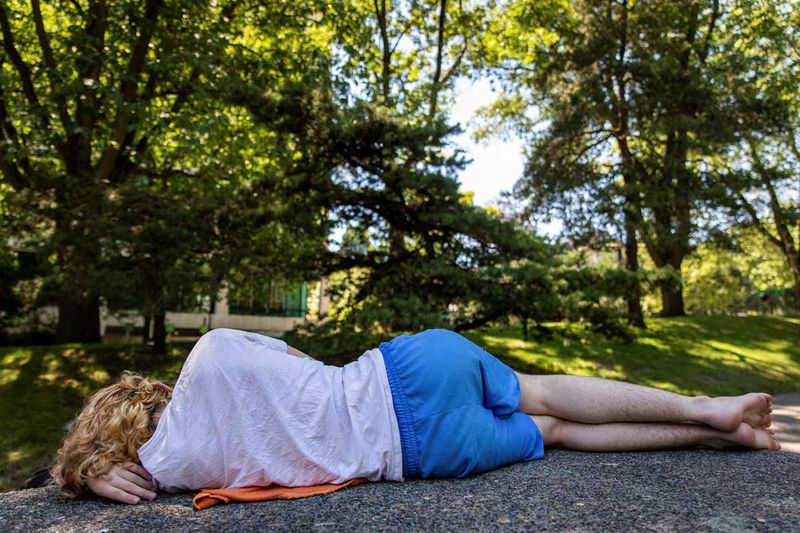 A young man naps in the shade during an unprecedented heat wave in Portland, Oregon.