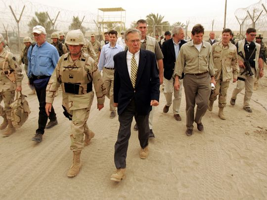 In this file photo taken on May 13, 2004 US Defence Secretary Donald Rumsfeld and Major General Geoffrey Miller (left), Deputy Director of detainee operations walk the grounds of the Abu Ghraib Prison, 30 kms west of Baghdad. Rumsfeld, who led the nation into war in Afghanistan and Iraq during the presidency of George W Bush, died at the age of 88 in New Mexico, his family announced June 30, 2021.