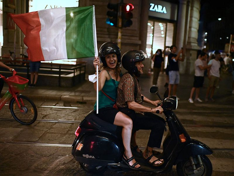 Italy's fans celebrate the victory of UEFA EURO 2020 semi-final football match between Italy and Spain near Piazza Duomo in Milan