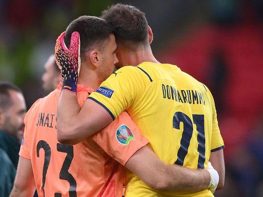 Spain's goalkeeper Unai Simon and Italy's goalkeeper Gianluigi Donnarumma embrace each other before the penalty shootout