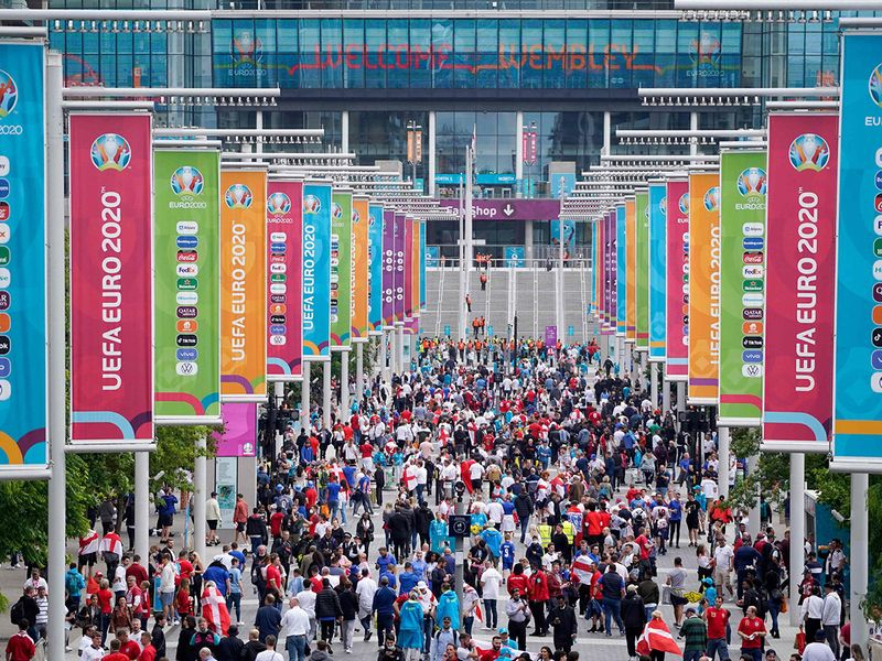 Supporters arrive to watch the Euro 2020 semi-final between England and Denmark at Wembley