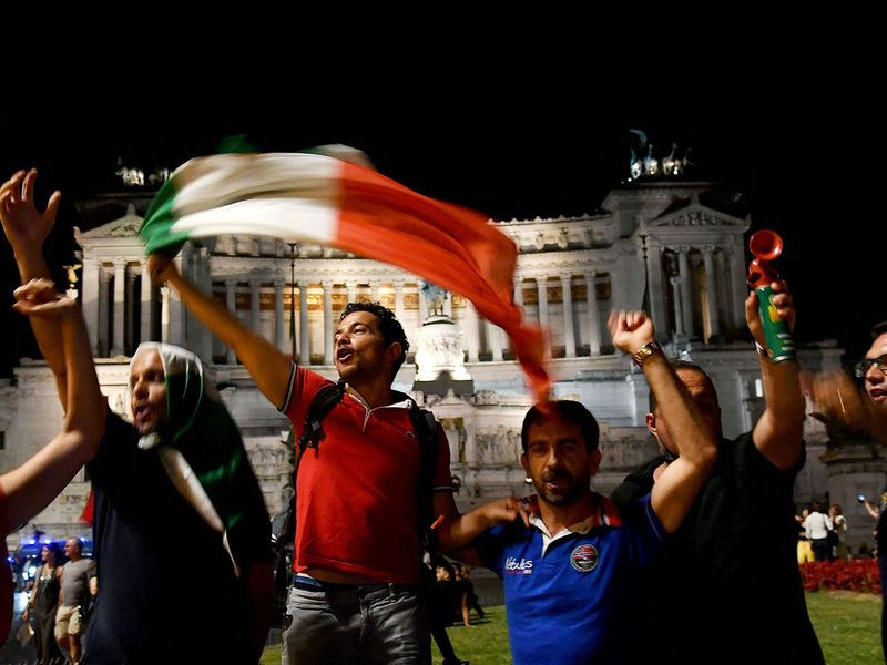 Supporters of Italy's national football team celebrate after Italy defeats Spain during the UEFA EURO 2020 semi-final at Piazza Venezia, in Rome, on July 6, 2021.