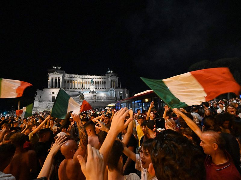Supporters of Italy's national football team celebrate defeating Spain