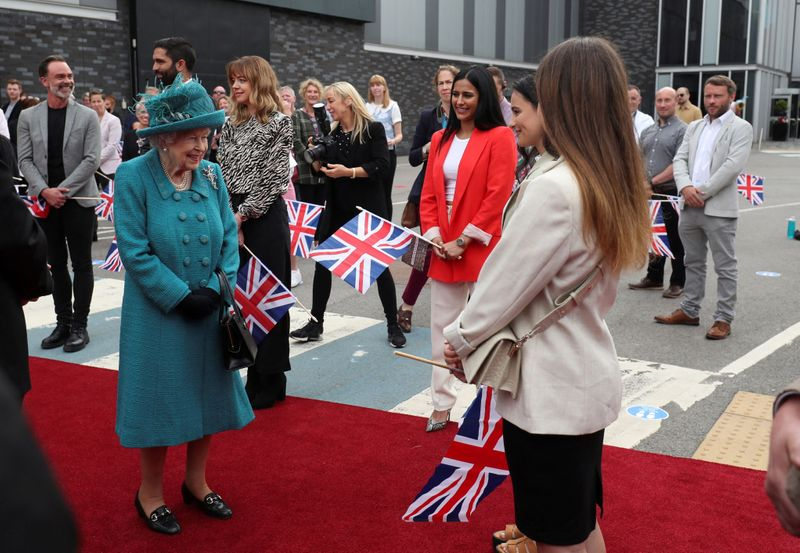 Britain's Queen Elizabeth II meets actors as she visits the set of the long running television series Coronation Street in Manchester, northwest England on July 8, 2021.