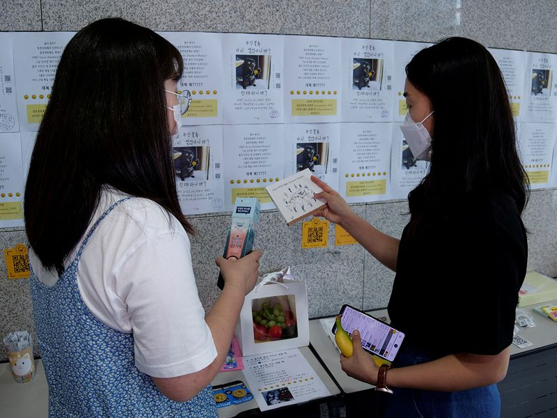 Women take a look at items at a faeces currency market at Ulsan National Institute of Science and Technology (UNIST) in Ulsan, South Korea.