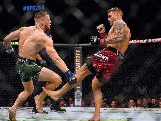 Dustin Poirier, right, kicks Conor McGregor during UFC 264