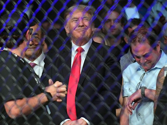 Former US President Donald Trump smirks as he is booed at UFC 264 at T-Mobile Arena