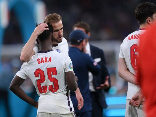 England's Harry Kane consoles Bukayo Saka after the penalty shootout against Italy in the Euro 2020 final