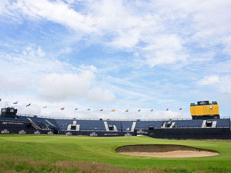 Flags flutter in the breeze above the empty stands around the 18th green during practice for The 149th British Open Golf Championship at Royal St George's, Sandwich in south-east England on July 12, 2021. (Photo by Paul ELLIS / AFP) / RESTRICTED TO EDITORIAL USE