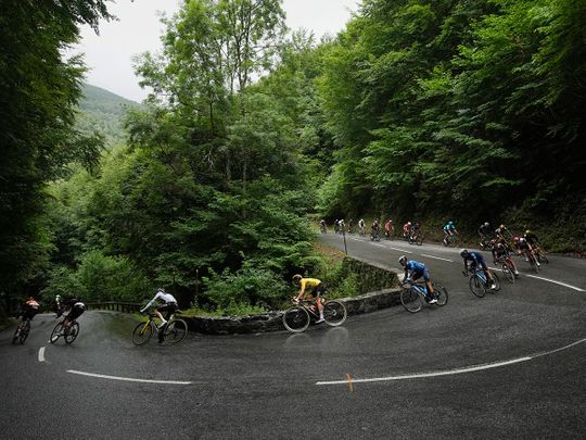 UAE Team Emirates' Tadej Pogacar, wearing the overall leader's yellow jersey, speeds downhill during Stage 16 of the Tour de France