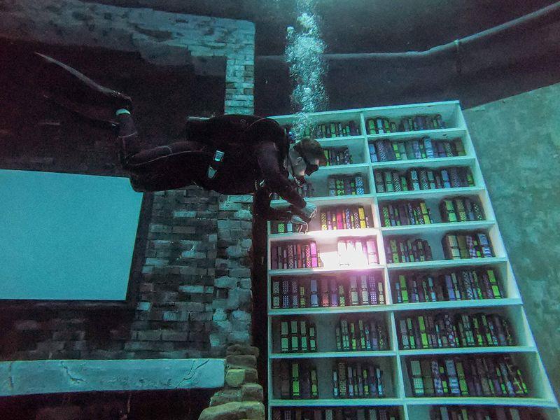 A diver browses mock books as he experiences Deep Dive Duba