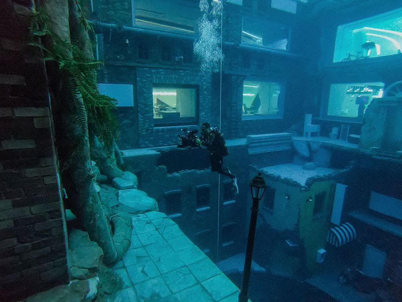 A diver captures images of a mock sunken city at Deep Dive.
