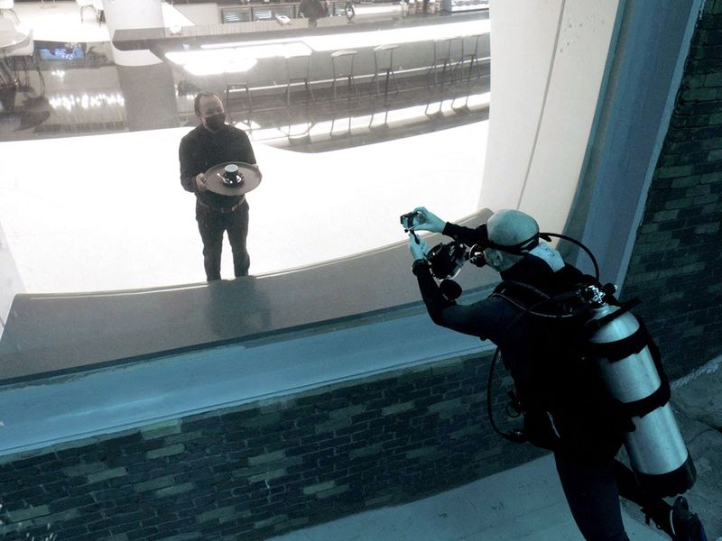 A diver experiencing Deep Dive, photographs a waiter through a viewing glass.