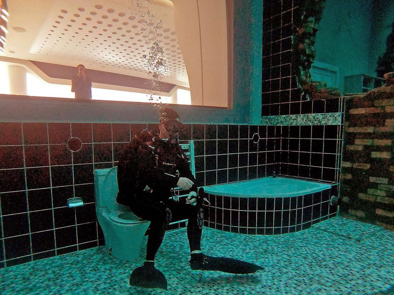 A diver explores a mock sunken city as he experiences Deep Dive Dubai, the deepest swimming pool in the world reaching 60m, in the United Arab Emirates, on July 10, 2021. - The city of superlatives, with the world's tallest tower among its many records, Dubai now has the deepest swimming pool on the planet complete with a