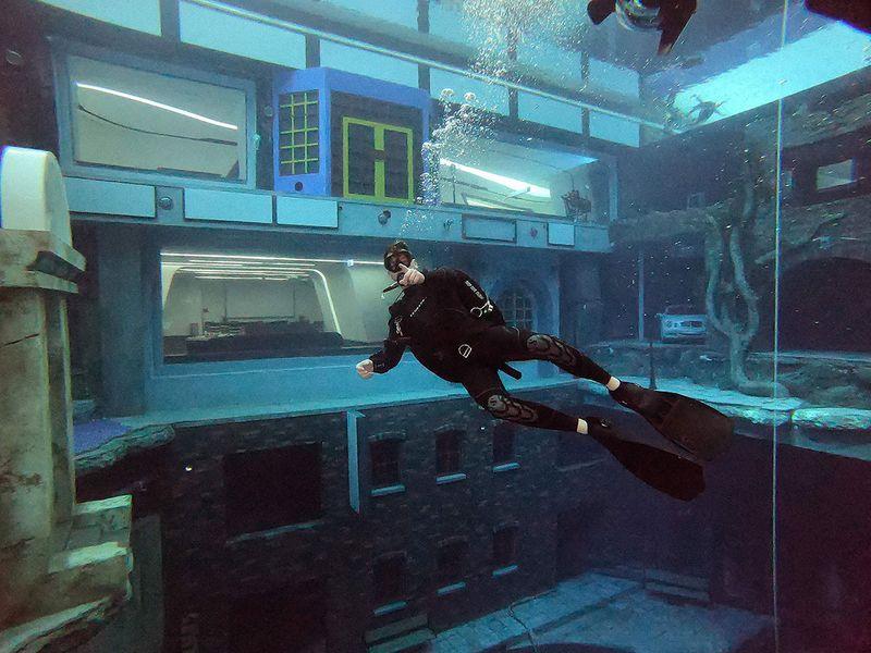 A diver explores a mock sunken city as he experiences Deep Dive Dubai