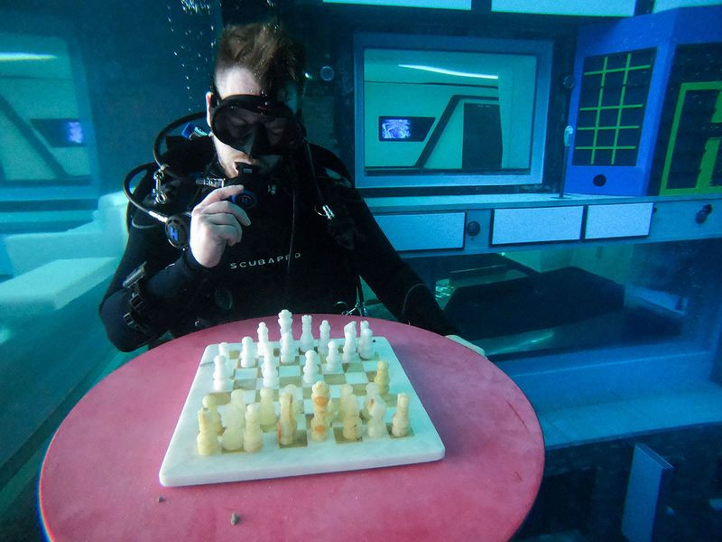 A diver plays mock chess as he experiences.