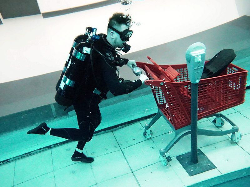 A diver uses a mock shopping cart as he experiences Deep Dive Dubai.