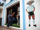 A fan kneels at the entrance to the first Mexico's church in memory of soccer legend Diego Maradona in San Andres Cholula, in Puebla state, Mexico.