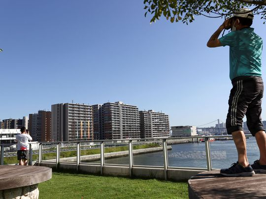 A man uses binoculars to look at the Athletes Village, where a person has tested positive for COVID-19, ahead of Tokyo 2020 Olympic Games