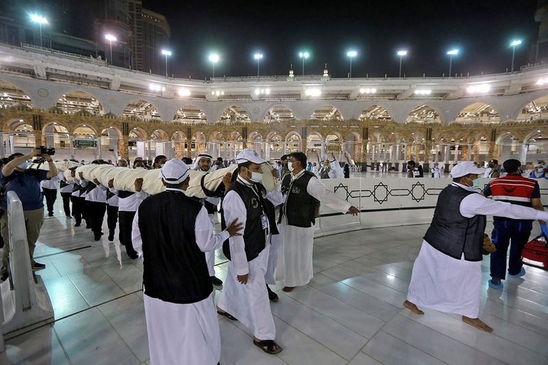 Labourers bring the new Kiswa, the protective cover that engulfs the Kaaba, made from black silk and gold thread and embroidered with Koran verses, in Saudi Arabia's holy city of Mecca on July 19, 2021 on the night before the start of the annual hajj pilgrimage. - The drape which engulfs the Kaaba is formally called Kiswa and is changed every year at the culmination of the annual hajj, or pilgrimage, when the pilgrims have left Mecca to go to Arafat, the starting point of their hajj journey.