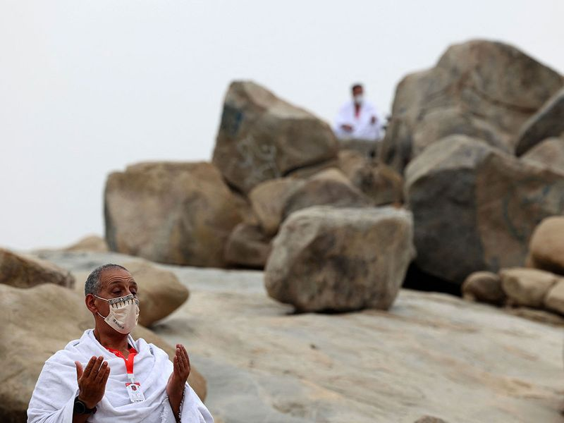 Mulism pilgrims pray next to Saudi Arabia's Mount Arafat, also known as Jabal al-Rahma (Mount of Mercy), southeast of the holy city of Mecca, during the climax of the Hajj pilgrimage amid the COVID-19 pandemic, on July 19, 2021. - Muslim pilgrims gathered around Saudi Arabia's Mount Arafat on Monday in the high point of this year's hajj, being held in downsized form and under coronavirus restrictions for the second year running. Just 60,000 people, all citizens or residents of Saudi Arabia, have been selected to take part in this year's hajj, with foreign pilgrims again barred.