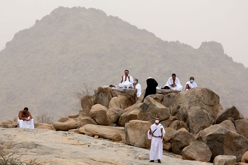 Muslim pilgrims pray near the rocky hill known as Mountain of Mercy, on the Plain of Arafat, during the annual hajj pilgrimage, near the holy city of Mecca, Saudi Arabia, Monday, July 19, 2021. Tens of thousands of vaccinated Muslim pilgrims circled Islam's holiest site in Mecca on Sunday, but remained socially distanced and wore masks as the coronavirus takes its toll on the hajj for a second year running. What once drew some 2.5 million Muslims from all walks of life from across the globe, the hajj pilgrimage is now almost unrecognizable in scale.