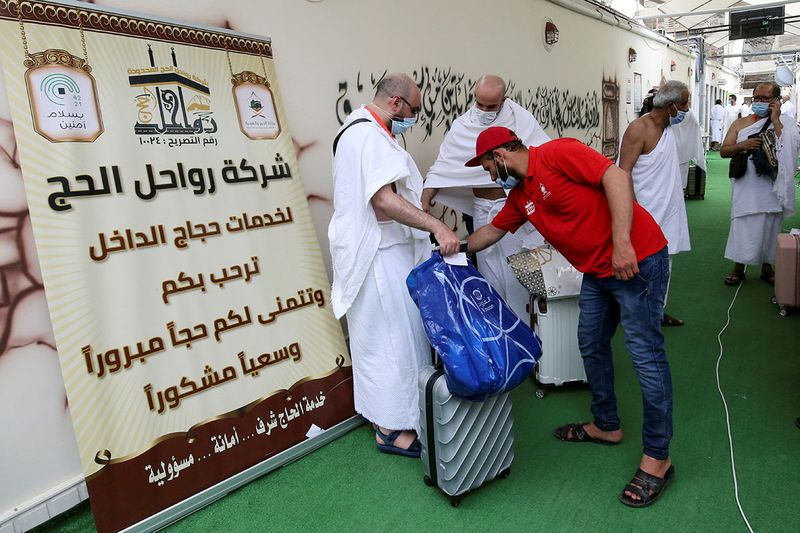 Pilgrims stand with their luggage as they arrive in the Mina area during the annual Haj pilgrimage, in the holy city of Mecca, Saudi Arabia, July 18, 2021.