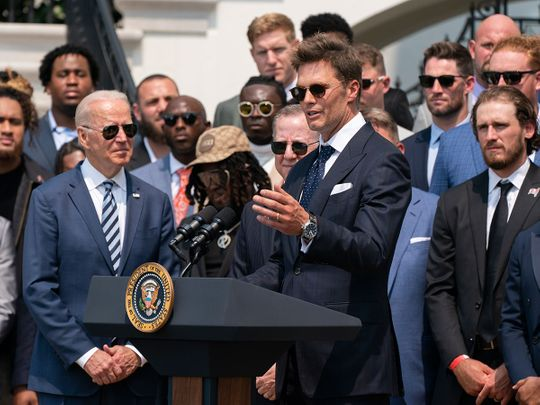President Joe Biden listens to Tampa Bay Buccaneers quarterback Tom Brady speak during a ceremony on the South Lawn of the White House