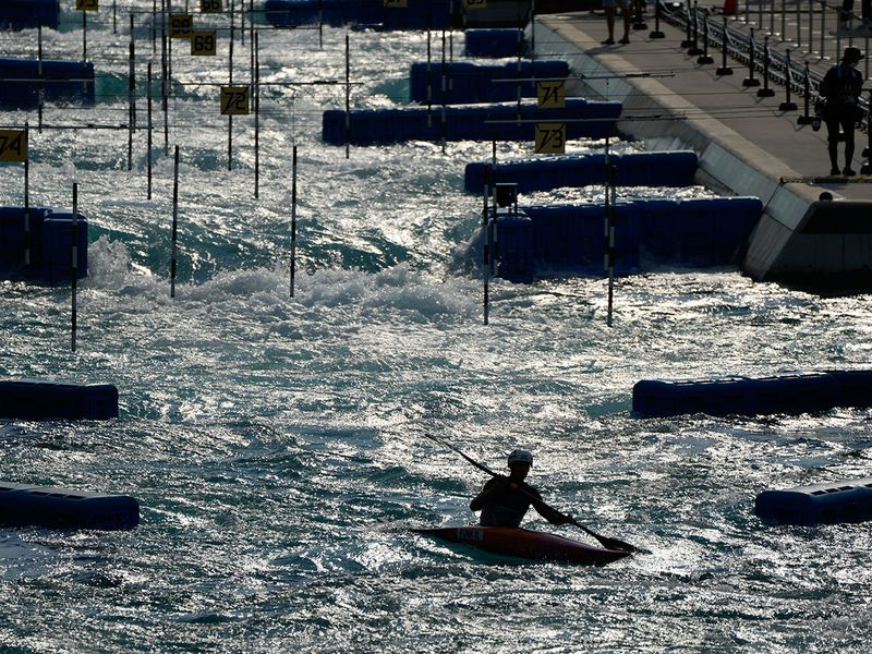 A kayaker is silhouetted at the end of a training session at the Kasai Canoe Slalom Centre