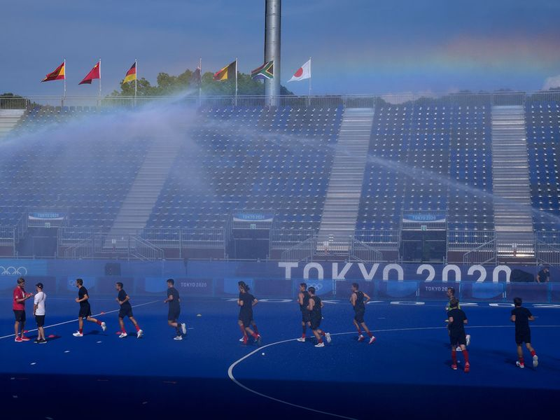Members of the Canadian men's field hockey team run beneath sprinklers during a training session at Oi Hockey Stadium