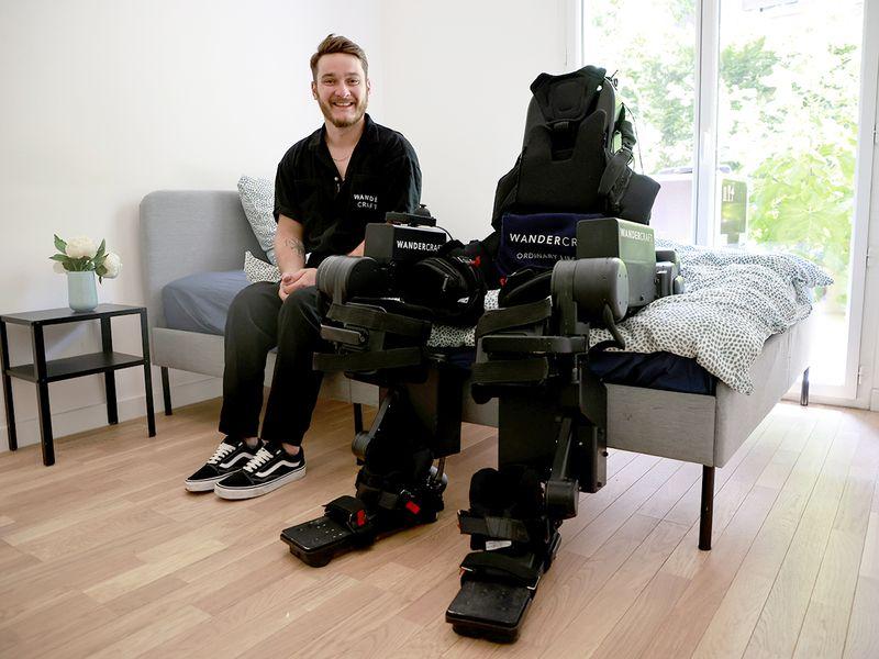Kevin Piette poses next to a robot exoskeleton