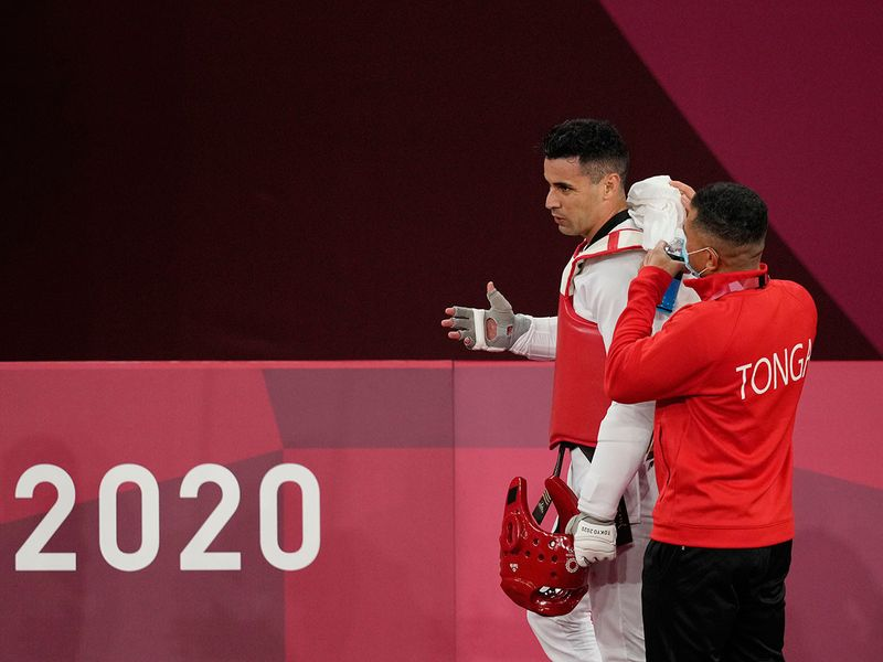 An unhappy Pita Taufatofua of Tonga leaves the ring site after his defeat by Slovenia's Ivan Trajkovic during the taekwondo men's 80kg competition
