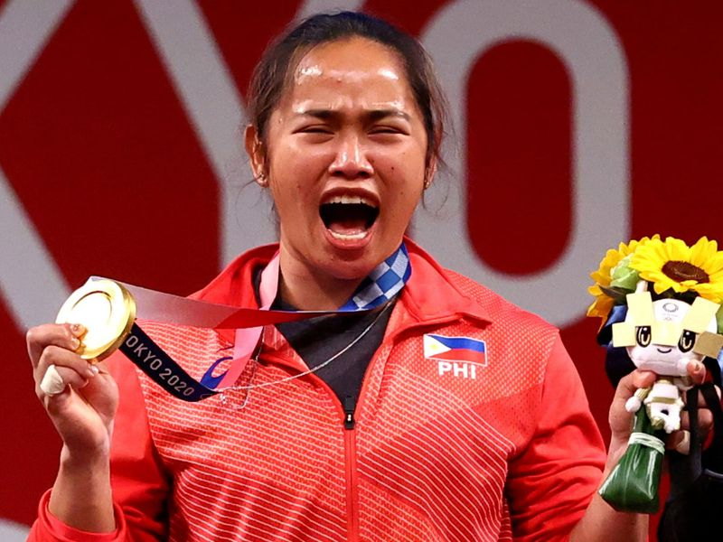 Hidilyn Diaz celebrates on the podium with her gold medal