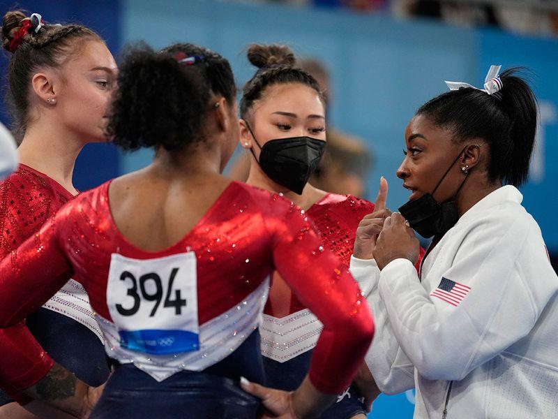 Simone Biles talks to US teammates Jordan Chiles, Sunisa Lee and Grace McCallum