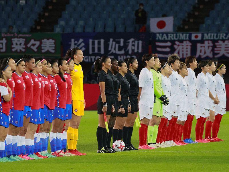 The Chile and Japan football teams line up for the national anthems at the Miyagi Stadium in Miyagi