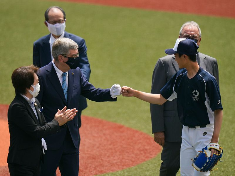 International Olympic Committee President Thomas Bach, left, fist bumps Yuma Takara before the baseball game between Japan and the Dominican Republic