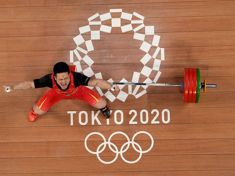 Shi Zhiyong of China celebrates after winning the gold medal in the men's 73kg weightlifting event