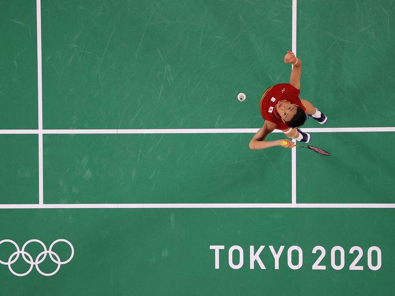 Japan's Kento Momota hits a shot to South Korea's Heo Kwang-hee
