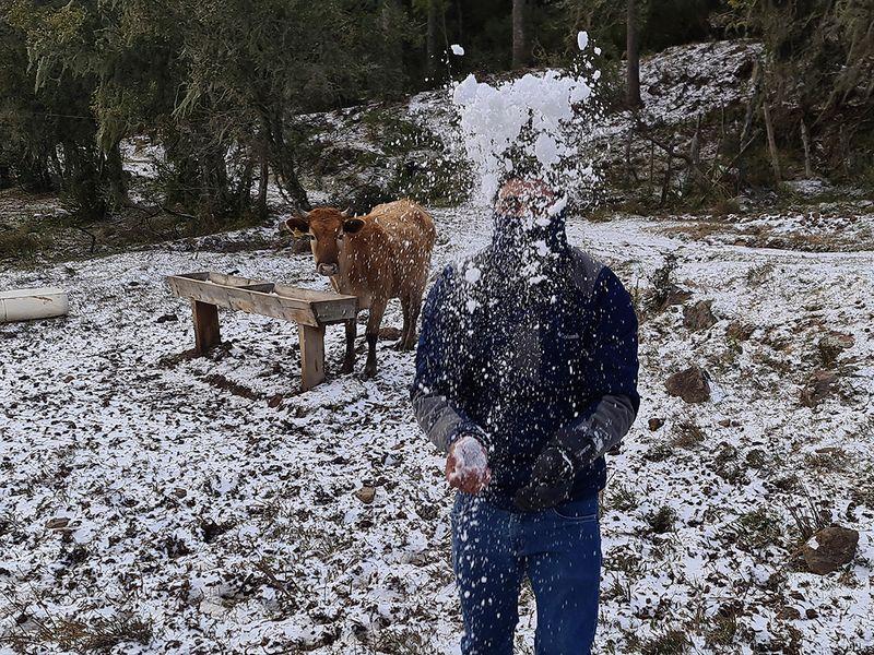 A man plays with snow at a farm in rural Sao Joaquim, Brazil.