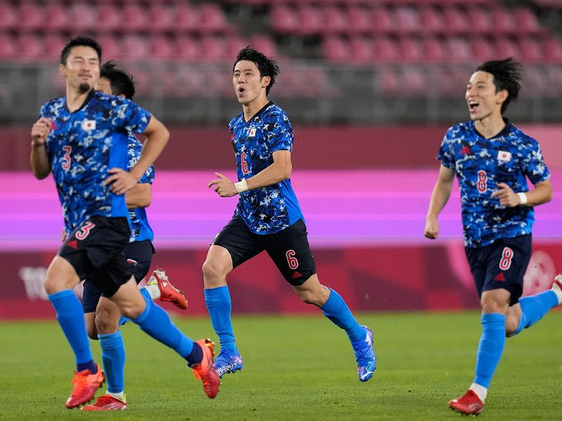 Japan celebrate after defeating New Zealand 4-2 on penalties in their football quarter-final in Kashima,
