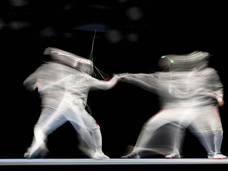 Japan's Chika Aoki competes against Tunisia's Yasmine Daghfous in the women's team sabre