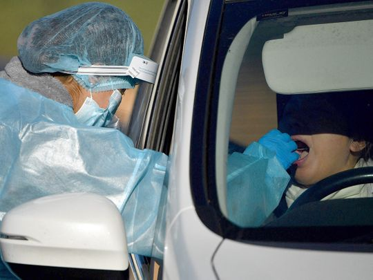 A health worker takes a swab sample from a resident at a COVID-19 drive-through testing site in western Sydney.