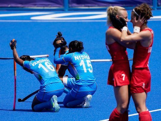 India's Vandana Katariya (16) and India's Nisha (15) kneel