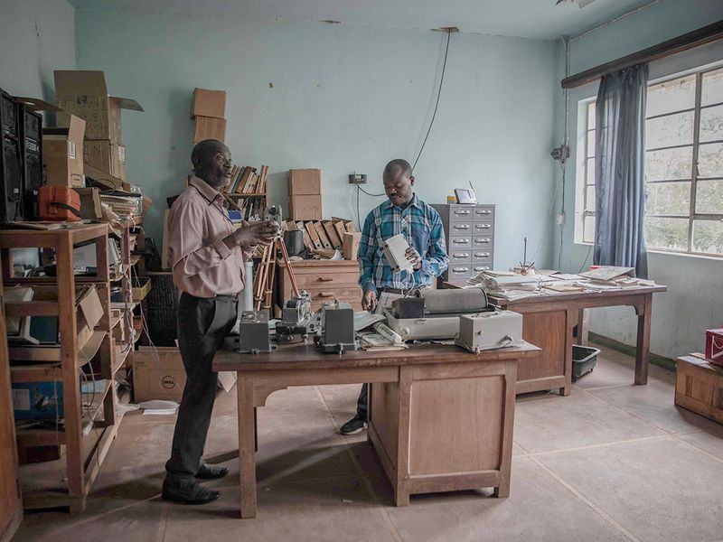Two researchers discuss in a room how the electronic seismograph works in the Natural Sciences Research Center (CRSN) of Lwiro.