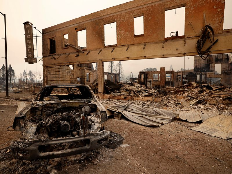 View of a burned out car and commercial building following the Dixie Fire, a wildfire that tore through the town of Greenville, California.