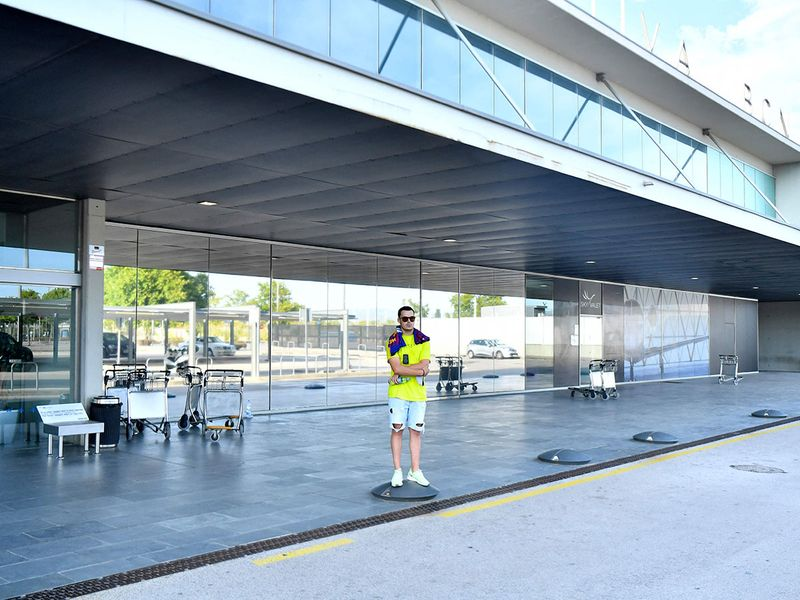 A lone Barcelona fan outside the city's airport as Lionel Messi heads to Paris