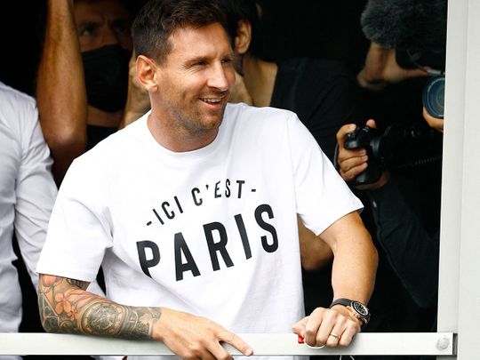 Argentinian football player Lionel Messi salutes supporters from a window after he landed at Le Bourget airport ahead of signing for PSG