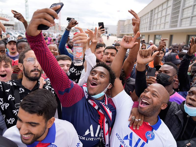 Paris St-Germain supporters wait for Lionel Messi to arrive at Le Bourget airport