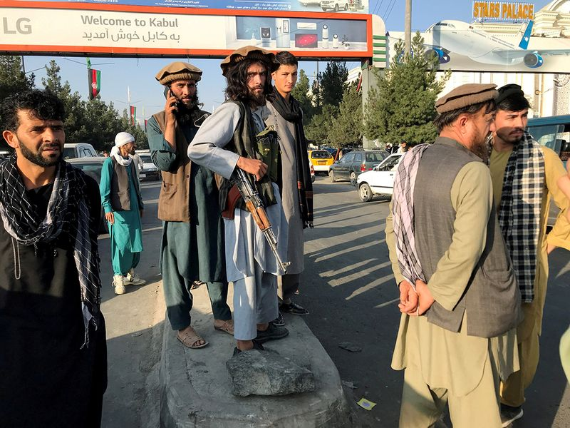 A member of Taliban (C) stands outside Hamid Karzai International Airport in Kabul, on August 16, 2021.