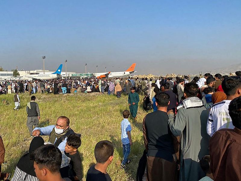 Afghans crowd at the airport as they wait to leave from Kabul on August 16, 2021.